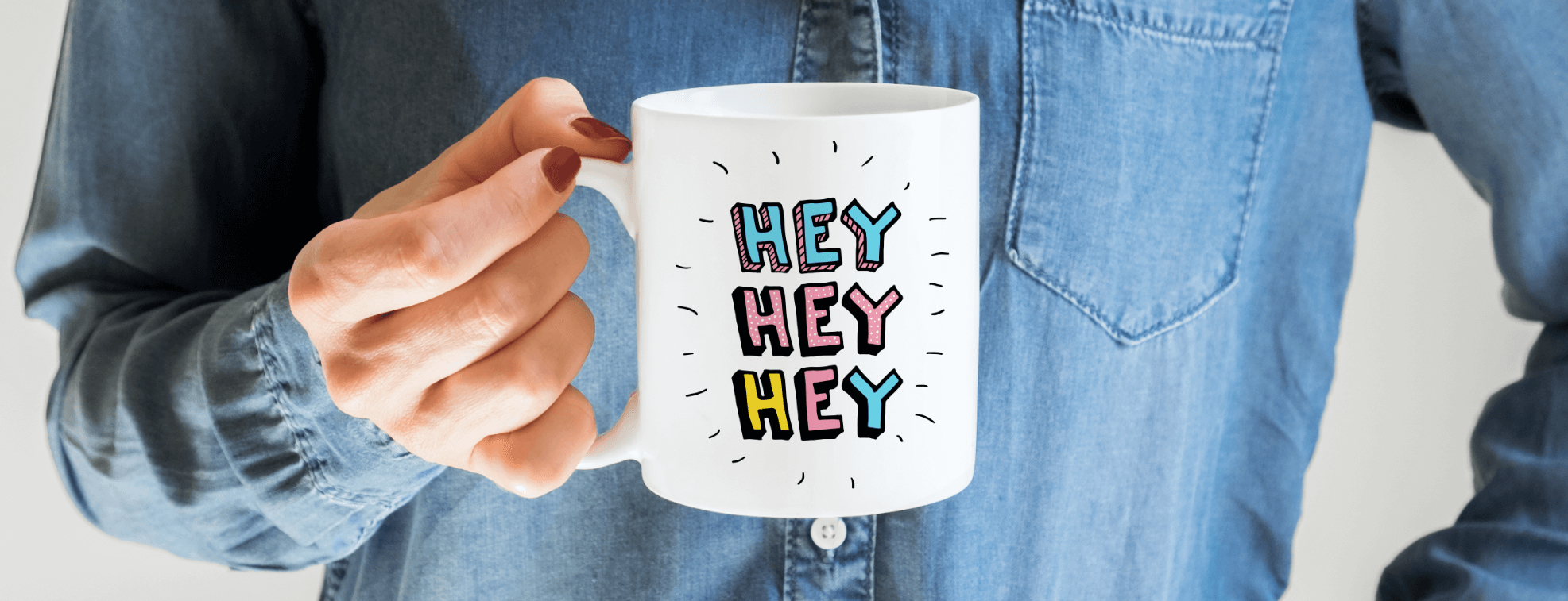 A woman holding a mug with Hey Hey Hey written on it
