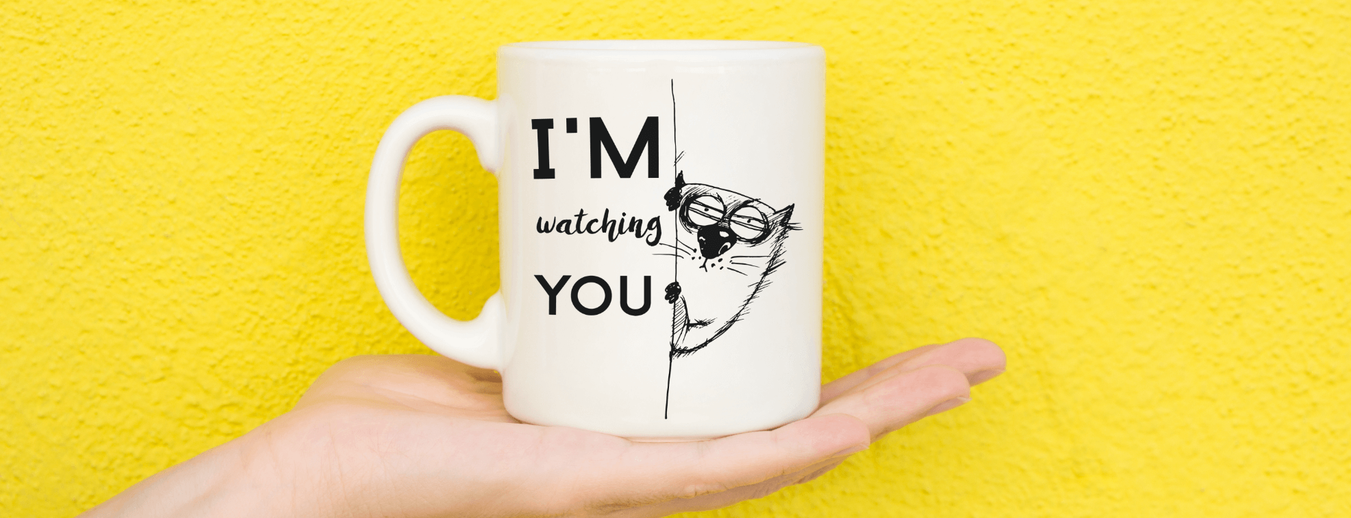 A funny mug on a yellow background with a cat watching you