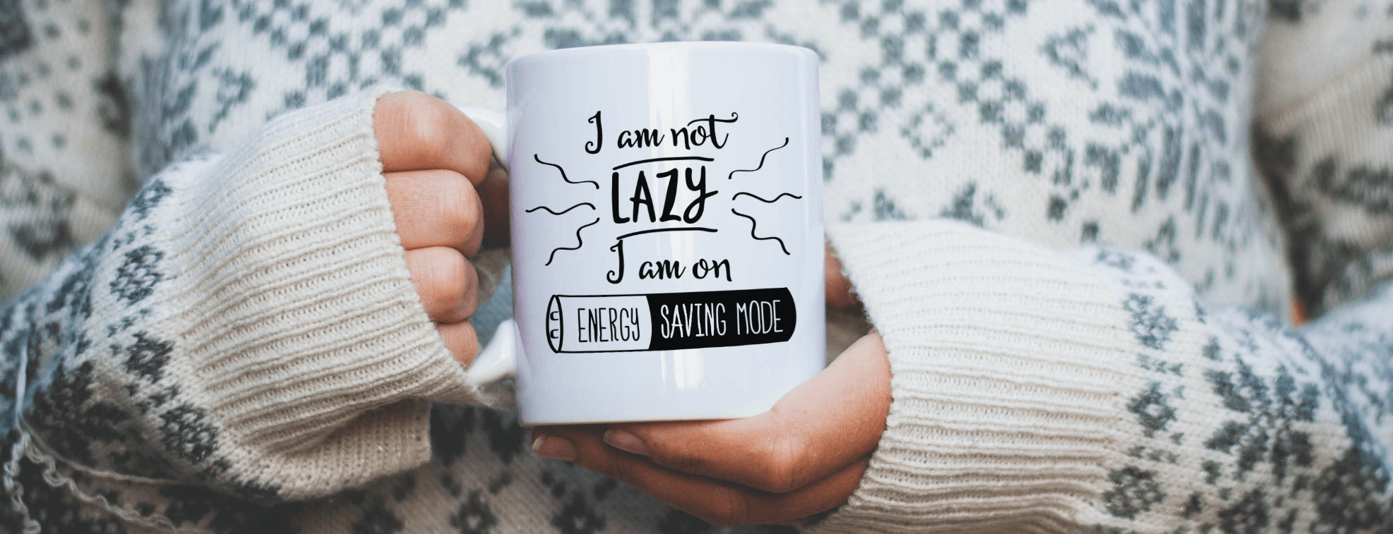 A girl in a cozy sweater holding a mug with 'I am not lazy I am on energy saving mode' written on it